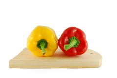 Two peppers on the board. Two peppers, red and yellow on the board stock photos
