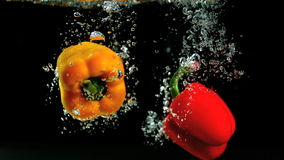 Two peppers falling in water and floating. In slow motion stock video