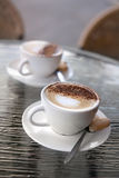 Two perfect cappuccinos. Served sitting on a glass table Royalty Free Stock Photography