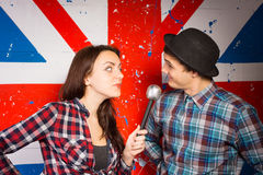 Two performers doing a British comedy show. Standing in front of a Union Jack painted on a wall using a microphone wearing patriotic clothing and a bowler hat Royalty Free Stock Image