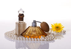 TWO PERFUME BOTTLES, PEARLS and YELLOW FLOWER Royalty Free Stock Image