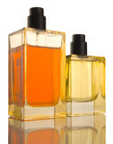 Two Perfume Bottles - reflection, patch. Two Perfume Bottles yellow and orange on white background, reflection Stock Image