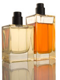Two Perfume Bottles - reflection, patch. Two Perfume Bottles yellow and orange on white background, reflection Stock Photo