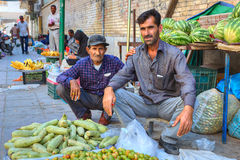 Two persian men sell vegetables and fruits sitting on sidewalk. Royalty Free Stock Photography