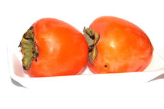 Two persimmons on a plate Royalty Free Stock Photography