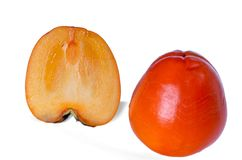 Two persimmons, whole, and a half, isolated on white stock photography