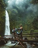 Two Person Carrying Black Inflatable Pool Float on Brown Wooden Bridge Near Waterfalls Stock Images