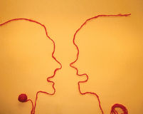 Two person communication - Red string. Two person communication or argumentation, made out of wool line. Ariadne's string is the symbol of finding the way out of Royalty Free Stock Photo