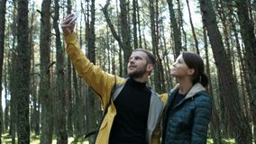 Tourists man and woman taking photo at phone. Two person: girlfriend and boyfriend making a pic at beauty natural background with treeline in beauty sunrise stock video footage
