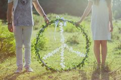 Two Person Holding White and Green Peace Wreath Stock Photo
