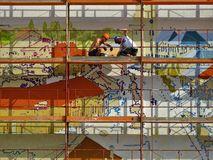 Two Person on Scaffolding Painting Wall royalty free stock photography