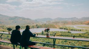 Two Person Sitting on Chair in Front of Lake and Mountains Stock Photo