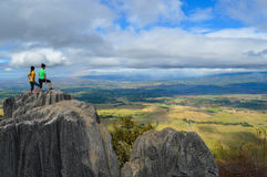 Two Person Standing at the Top of Rock Formation during Daytime Royalty Free Stock Images