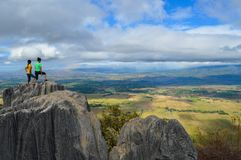 Two Person Standing at the Top of Rock Formation during Daytime Royalty Free Stock Photography