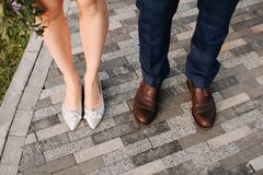 Wedding shoes , feet man and woman on the stone road royalty free stock images