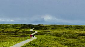 Two Person Walking On Path Under Blue Sky Royalty Free Stock Image