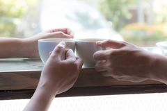 Two persons as couple drinking hot coffee together. By sitting near window of cafe Royalty Free Stock Images