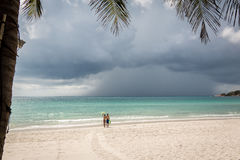 Two persons on the beach see a thunderstorm comming. Haad Rin, Koh Pangan, May 04, Thailand Royalty Free Stock Photos