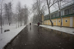 Two persons on bicycles running out of a weather phenomena - sno Stock Photography