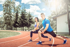 Two persons doing stretching excercise outdoor. Royalty Free Stock Photos