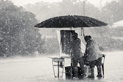 Two persons endure struggle on obstacles rainstorm Royalty Free Stock Image
