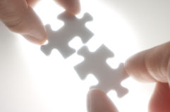 Two persons fitting puzzle pieces against the ligh Royalty Free Stock Images