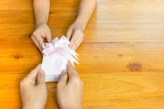 Two persons hands giving and receiving a present gift box on table. stock image
