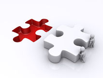 Two persons are pushing last puzzle piece Royalty Free Stock Image