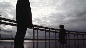 Two persons silhouettes standing on river shore with highway bridge. Two persons silhouettes in winter jackets standing on river shore with highway bridge on stock video