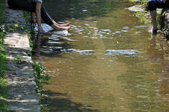 Two persons having their feet in a river to cool down. Two persons sitting on a paved Riverside, Swinging their feet into the watrer to refresh and cool down stock photography