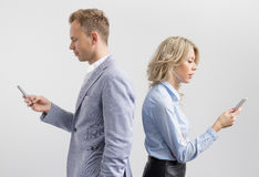 Two persons too busy with their mobile phones Royalty Free Stock Photos