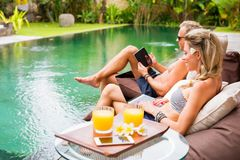 Two persons using tech gadgets by the pool. Couple working with computer and tablet by the pool Stock Photos
