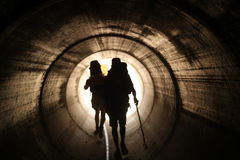 Two persons walk to the light in the end of the tunnel Royalty Free Stock Images