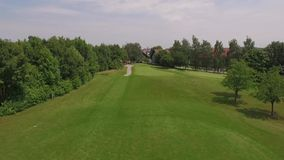 Two persons walking at the golf course. Drone flies above two golf player walking across the golf course in the direction of the golf club stock footage