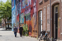 Two persons walking next to a graffiti wall in Rotterdam city center Stock Images