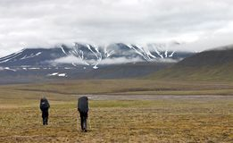 Two persons walking in tundra on Svalbard Stock Photo