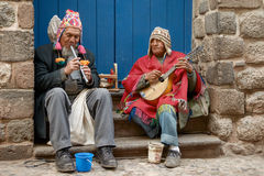 Two peruvian blind musicians playing flute and mandoline in the street of Cusco, Peru Royalty Free Stock Images