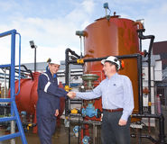 Two petrochemical contractors closing a deal. In front of an oil refinary. Outdoor stock photos
