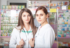 Two pharmacist greating the clients Royalty Free Stock Images