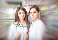 Two pharmacist greating the clients Royalty Free Stock Photo