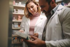 Pharmacists searching for a medication in the store. Two pharmacist holding prescription and checking medicine in pharmacy store. Man and women pharmacists stock images