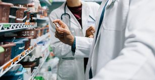 Two pharmacist looking for critical medicinal drug Stock Photography