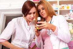 Two pharmacist woman looking at bottle Stock Image