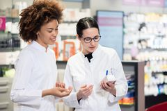 Two pharmacists analyzing the package of a new pharmaceutical drug. Two experienced female pharmacists wearing lab coats while analyzing together the package of Royalty Free Stock Photography