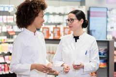 Two pharmacists analyzing the package of a new pharmaceutical drug. Two experienced female pharmacists wearing lab coats while analyzing together the package of Royalty Free Stock Photos