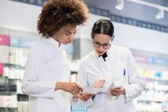 Two pharmacists comparing medicines regarding indications and side effects. Two female pharmacists reading the information from the pack of a new product while royalty free stock image