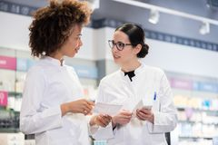 Two pharmacists comparing medicines regarding indications and side effects. Two female pharmacists reading the information from the pack of a new product while royalty free stock photography