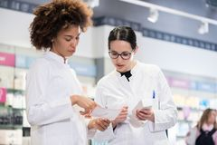 Two pharmacists comparing medicines regarding indications and side effects. Two female pharmacists reading the information from the pack of a new product while stock image