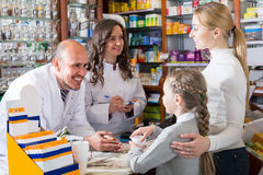 Two pharmacists and customers stock photos