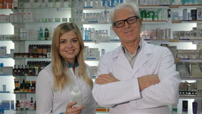 Two pharmacists pose at the drugstore. Two pharmacists posing at the drugstore. Senior male druggist in medical uniform crossing his arms on hist chest. Pretty stock video